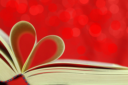 An open book with two pages folded together in the shape of a heart.