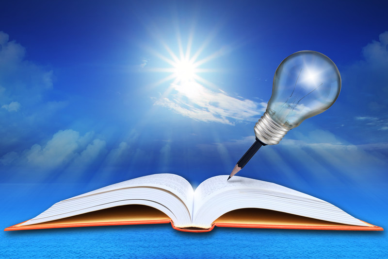 An image of a pen with a light bulb on top writing in a book.
