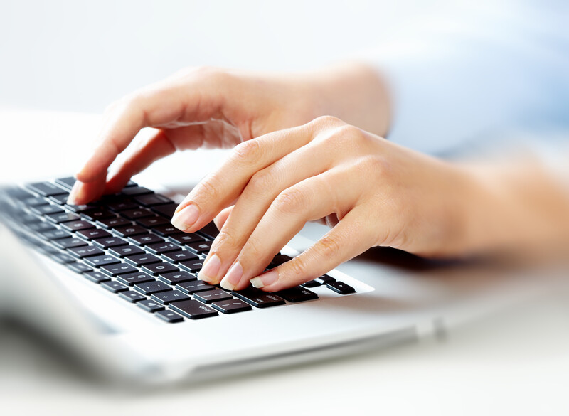 Photo of hands on a computer keyboard.