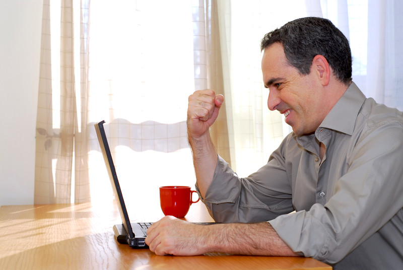 A photo of a man sitting in front of a computer.