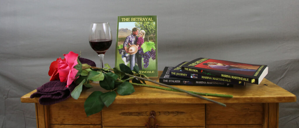 A photo of books, a red rose, and a glass of wine on top of a table.