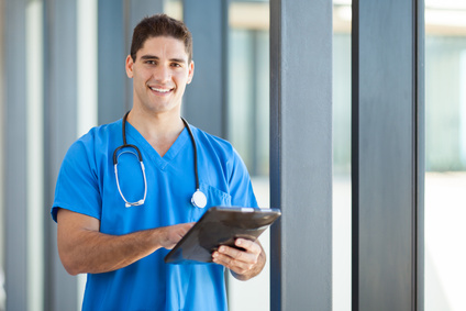 A man working in healthcare holding a tablet.