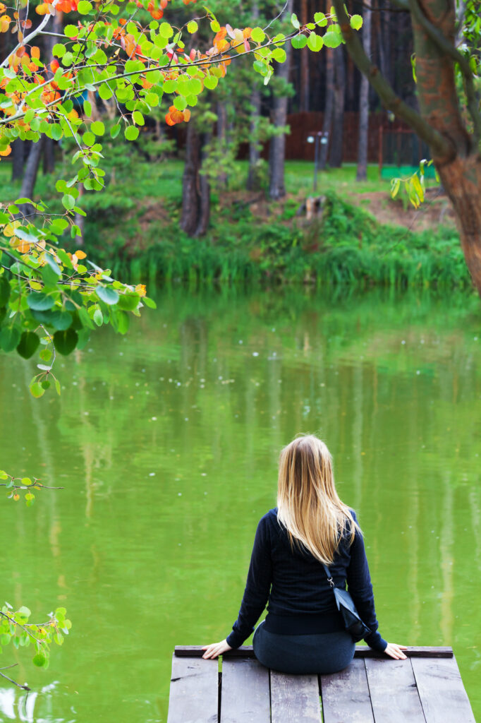 Photo of a lonely woman sitting in front of a pond.