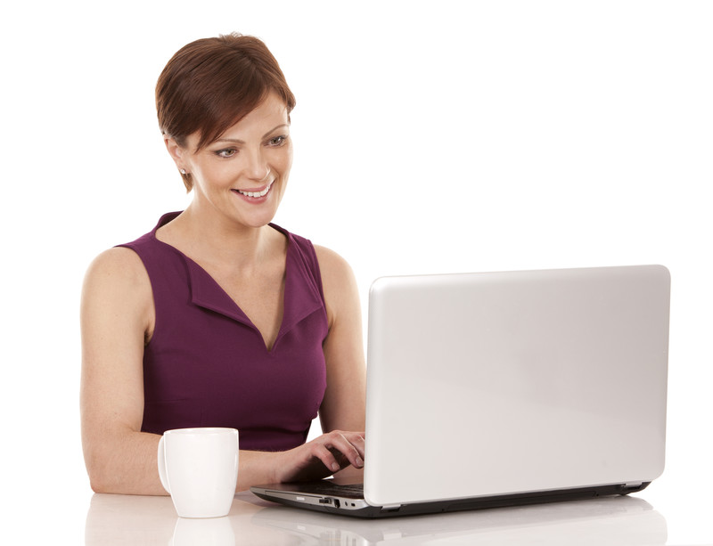 A photo of a smiling woman typing on a computer.