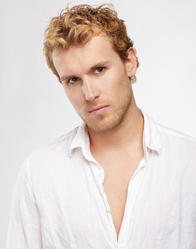 A young man with blonde hair in front of a light background.