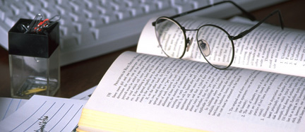 A photo of a pair of glasses on top of an open book placed in front of a computer.