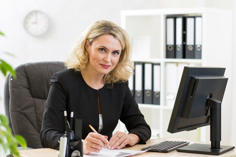 A woman with blonde hair sitting in front of a computer.